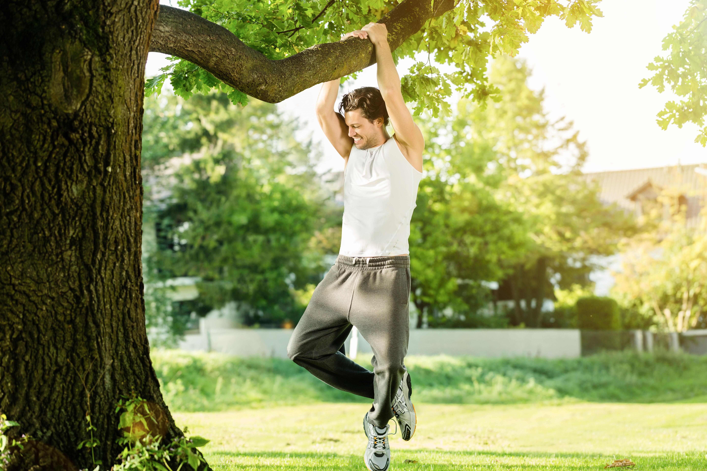 Mann Kommandoklimmzug am Baum